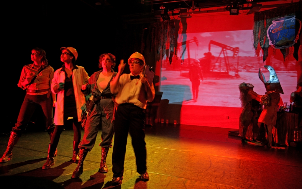 four queers dressed as engineers stand on a stage bathed in red light. Behind them is a projection of an oil well and a water nymph and salmon having a drink at the bar.